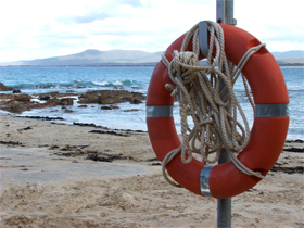 Life preserver on post beside beach/ocean